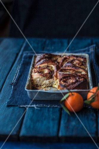 Apple and cinnamon buns in a baking try next to mandarins