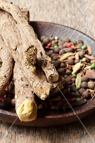 Mixed spices in a rustic wooden dish with liquorice root on top