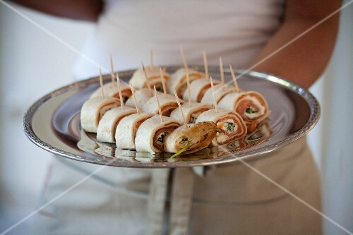 A waitress serving crepe rolls filled with salmon on a silver tray
