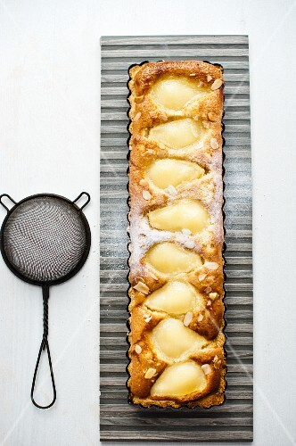 Pear and almond tart with icing sugar