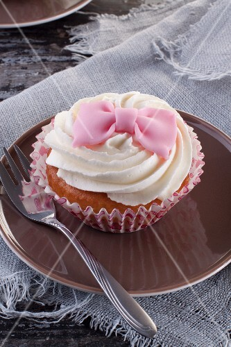 A cupcake decorated with a pink fondant bow