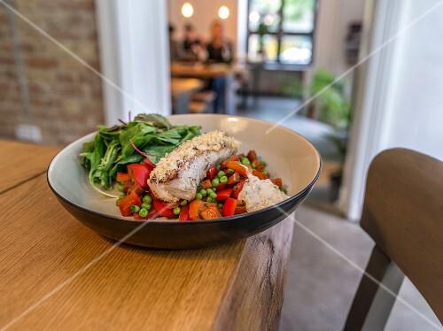 Paniertes Fischfilet auf Gemüse im Restaurant
