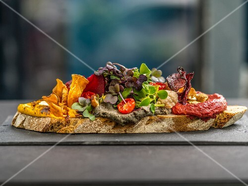 A slice of bread topped with spread, vegetable crisps and cress