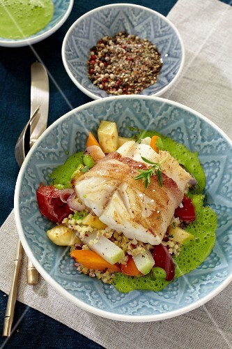 Cod wrapped in bacon on a bed of couscous with vegetables