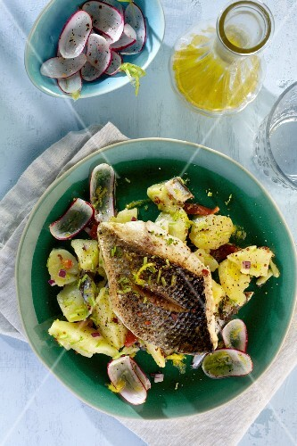 Seabass fillet on a potato and radish salad with apples