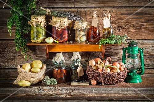 Various preserved vegetables and mushrooms on a wooden shelf