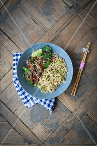 Fried noodles with beef, mange tout, sesame seed and spring onions (Asia)