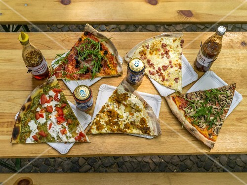 Various slices of pizza on a rustic wooden table