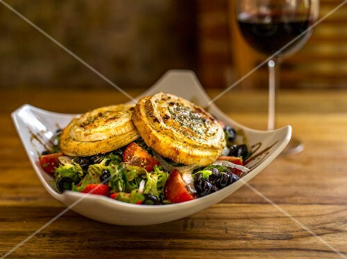 A mixed salad with tomatoes, olives and cheese quiche