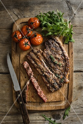 Grilled beef steak with tomatoes and rocket on a chopping board