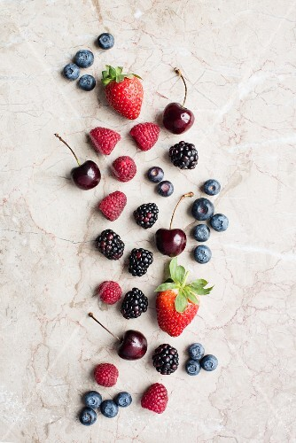 Various fresh berries and cherries on a stone surface