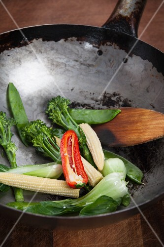 Oriental vegetables and a spatula in a wok