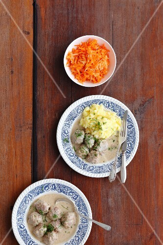 Meatballs in a mustard sauce with mashed potatoes and a carrot salad