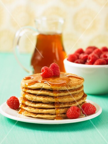 A stack of pancakes with raspberries and maple syrup