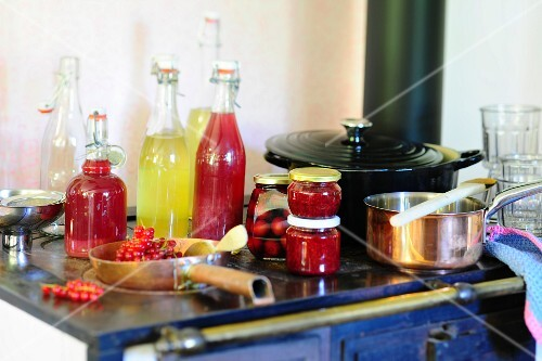 Various homemade fruit juices and preserved fruit on an old stove