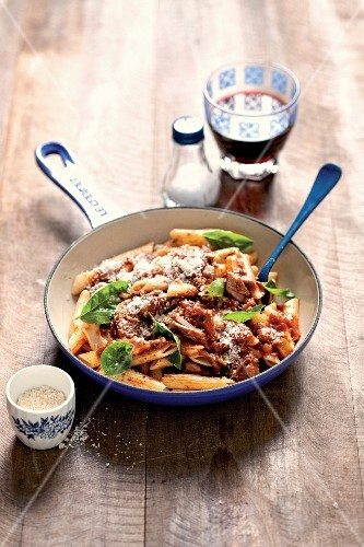 Penne pasta with beef ragout, Parmesan cheese and basil
