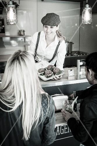 Junge Frau verkauft Snacks im Food Truck
