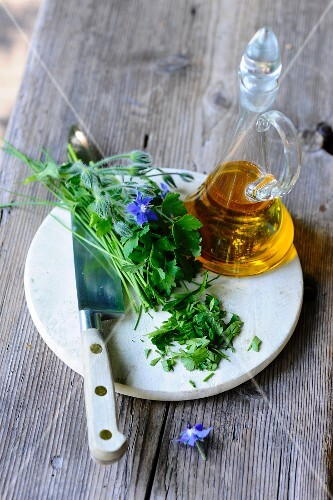 Fresh herbs, a knife and a carafe of oil on a wooden table