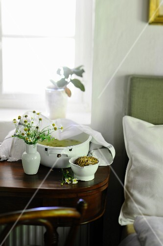 Chamomile tea to treat a cold on a bedside table