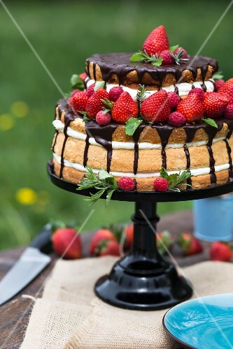 A naked cake with strawberries, cream and chocolate glaze
