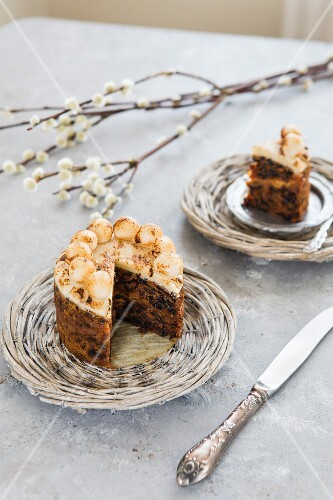 Simnal cake on a wicker plate with a sprig of catkins