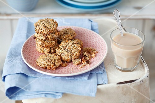 Muesli biscuits with chia seeds, sesame seeds, flaked almonds and dried lingonberries and a glass of cafe au lait