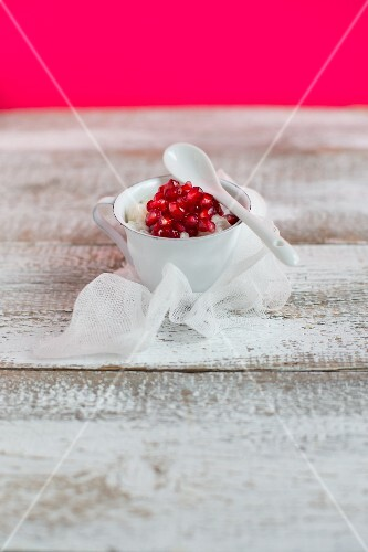 Coconut rice pudding with pomegranate seeds in a cup