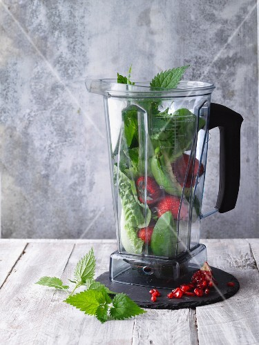 A blender filled with herbs, salad and fruit for smoothies