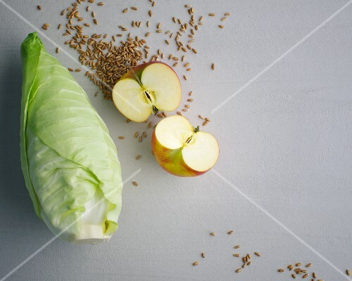 Grains, pointed cabbage and a halved apple