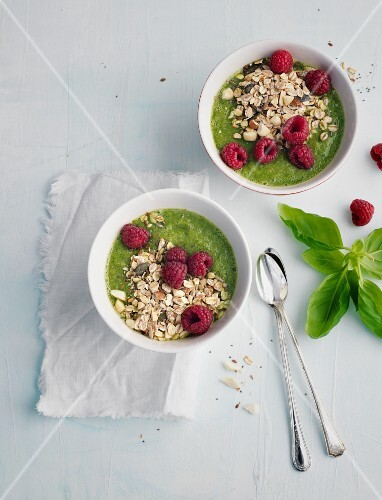 Bowls of smoothies with basil, cereals and raspberries