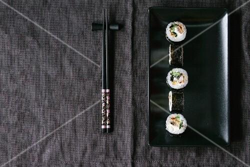 Maki sushi on a black plate next to chopsticks (Japan)