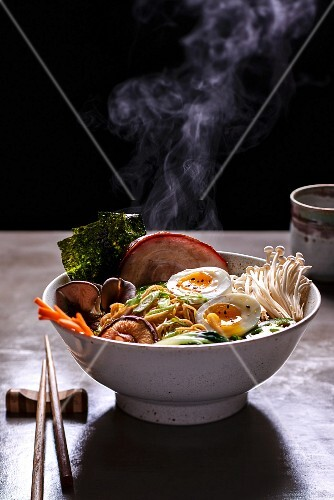 A steaming bowl of ramen noodle soup with mushrooms, prawns, pork belly and egg (Japan)