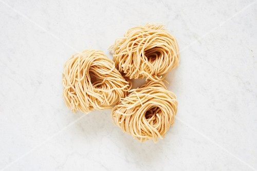 Fresh Pasta: three pasta nests on a white surface (seen from above)