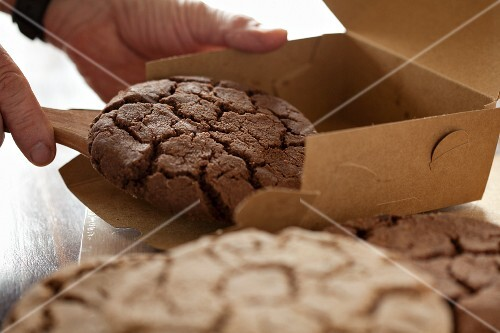 A man placing chocolate chip cookies into a box