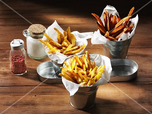 Three types of chips with a salt shaker and pink pepper on a rustic wooden surface