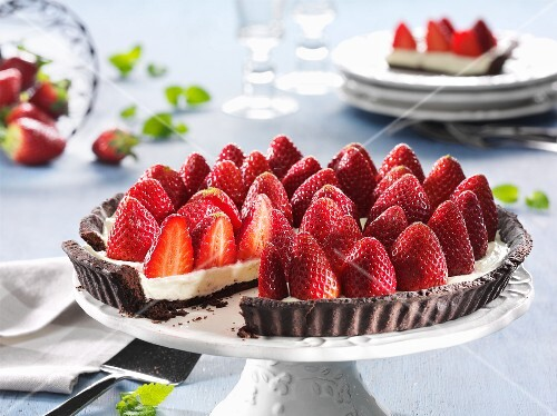 Strawberry tart, sliced, on a cake stand