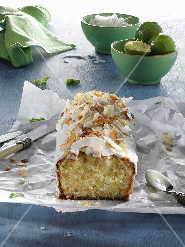 Lime and coconut cake, sliced, on a piece of paper on a blue wooden table