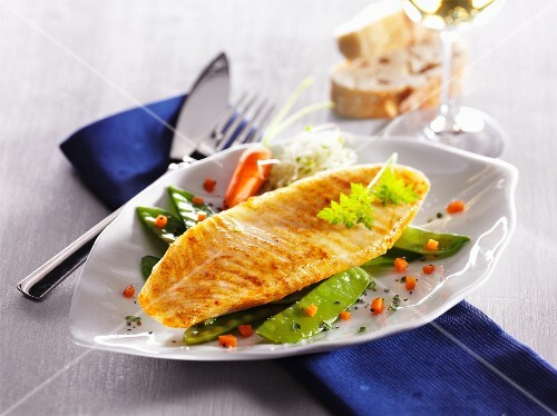 Catfish fillet on a bed of mange tout and carrots on a ceramic plate