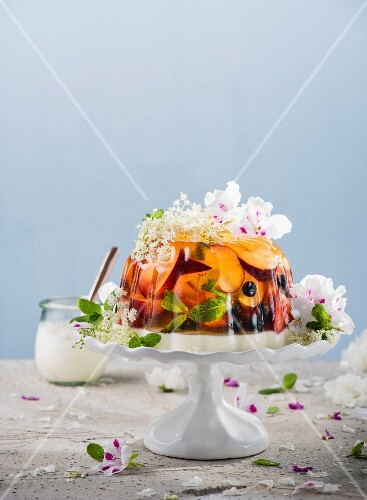 Wine jelly with plums and berries on a cake stand