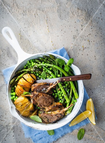 Lamb chops with potatoes, peas and asparagus in a pan