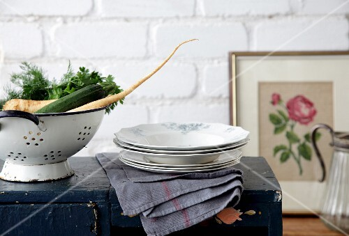 A stack of plates and a colander on an old wooden box