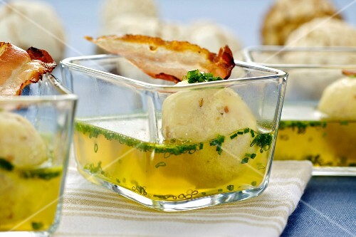 Soup with bacon and semolina dumplings in small glass bowls
