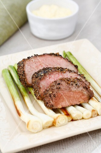 Peppered steak with oven-roasted spring onions