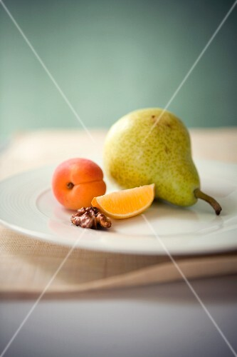 An arrangement featuring a pear, an apricot, an orange wedge and half a walnut
