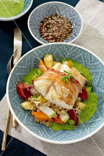 Cod wrapped in bacon on a bed of vegetables and couscous with green sauce