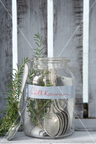 Silver spoons and rosemary in mason jar with welcome sign