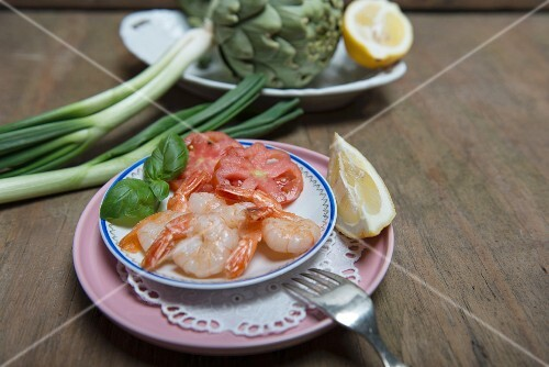 King prawns on a plate with sliced tomatoes, lemon and fresh basil with a bowl of artichokes, lemons and spring onions in the background
