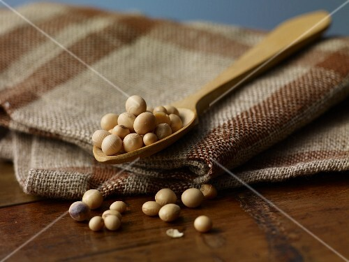 Soya beans on a wooden spoon on a jute cloth
