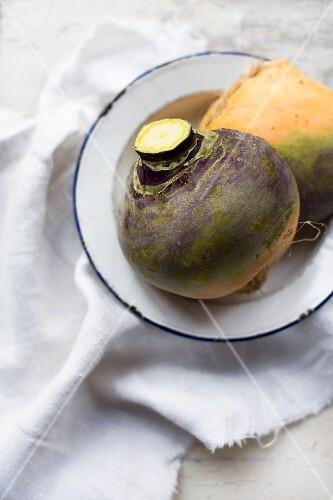 Organic turnips on an enamel plate on a linen cloth