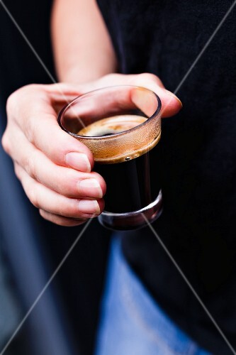 A hand holding a glass of coffee
